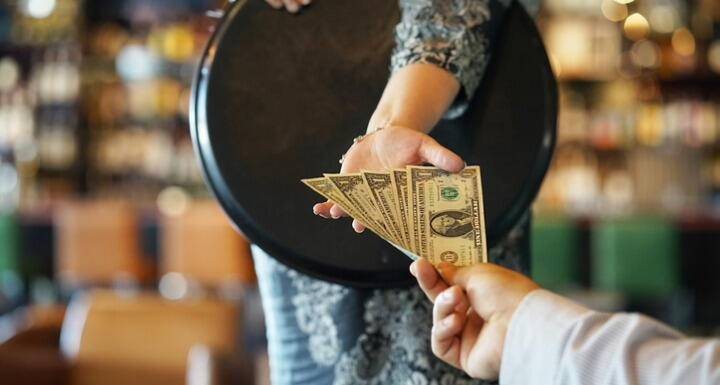 Waitress accepting a tip of multiple dollar bills from a customer