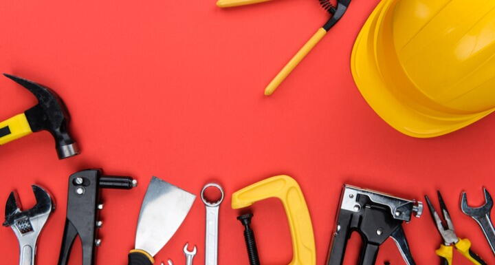 Different Tools and a yellow hard hat on Red Background