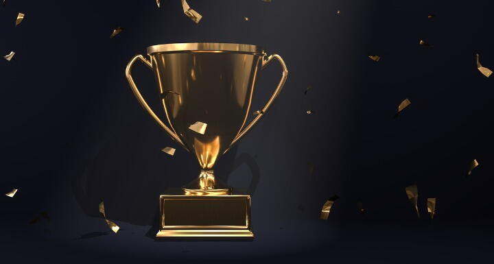 Gold trophy with gold confetti on black background