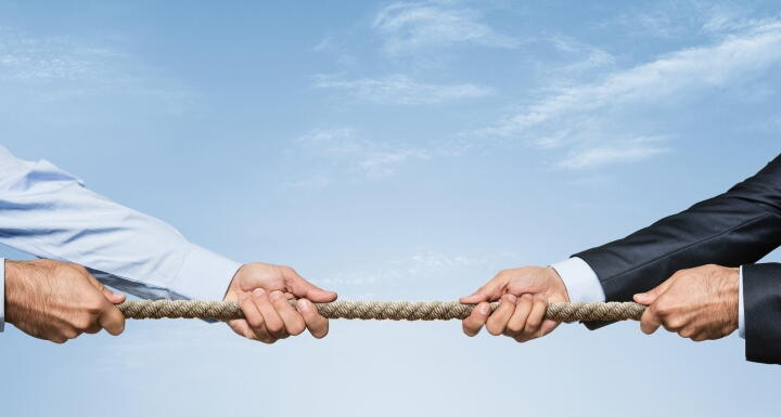 Business people tug of war with rope