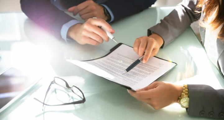 Two business people analyzing a document