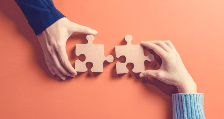 Two hands holding jigsaw on orange background