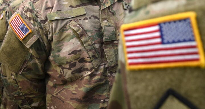 A close up of the American flag on the fatigue uniform of military personnel