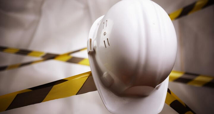 White construction hat sitting on tool with black and yellow tape in backgroun
