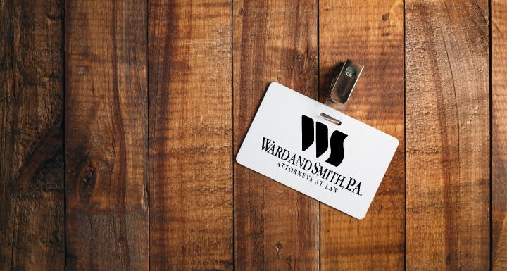 An employee badge for Ward and Smith on a wooden desk