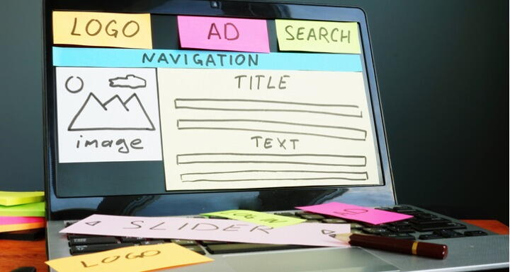 Laptop screen with sticky notes used to layout a website design