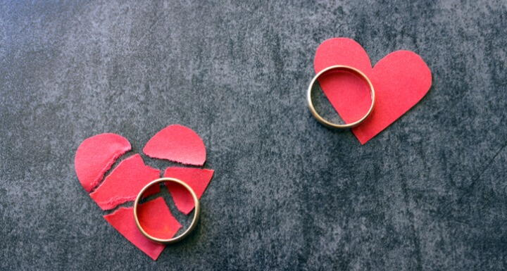 Two wedding rings on torn paper broken red hearts