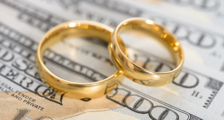 Two wedding bands on hundred dollar bills