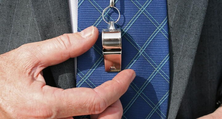 Lose up of businessman suit lapel with hanging whistle