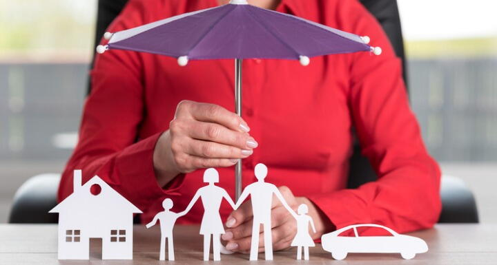 Woman holding a toy umbrella over a set of paper dolls and their paper house and car