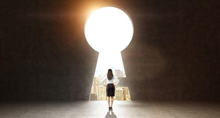 Silhouette of a woman standing in front of an oversized keyhole