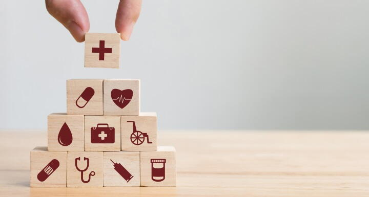 Wood blocks with health care icons stacked in pyramid with a hand placing the top block