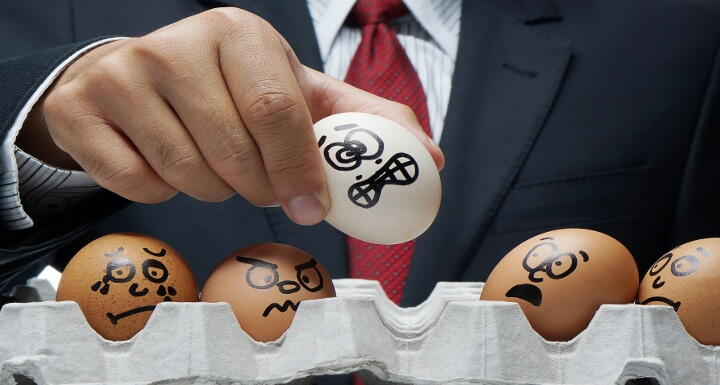 Man in business suit holding egg with an unhappy face drawn on it as other eggs remain in container