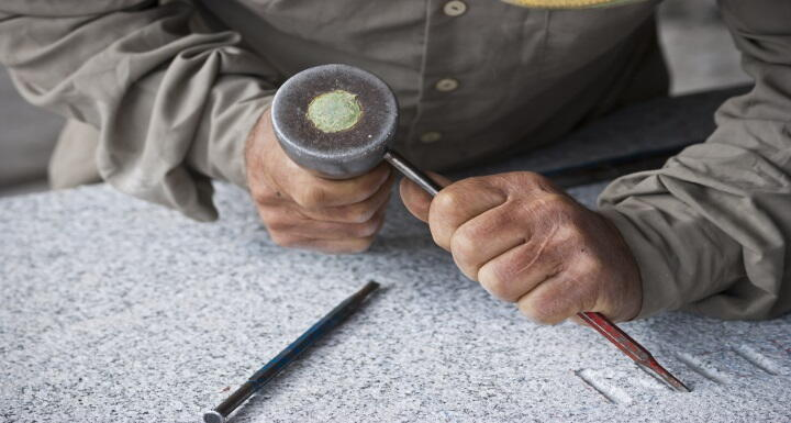 A stonemason working on granite with a chisel