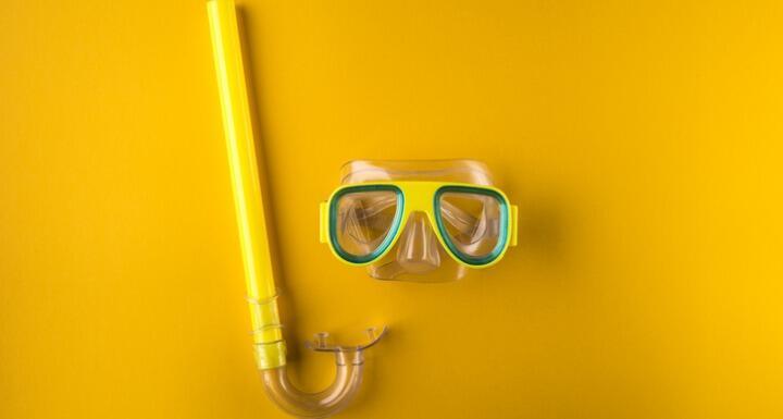 Yellow snorkeling mask on yellow background