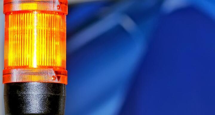 Yellow caution light on blue background