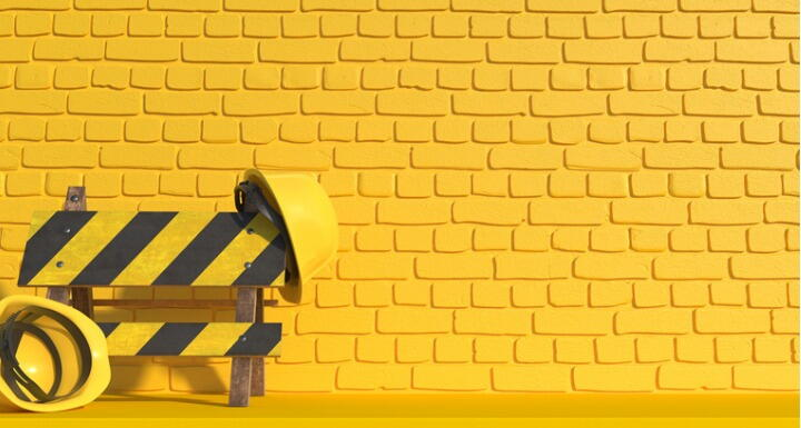 Yellow hard hats on yellow caution barrier in front of yellow brick wall