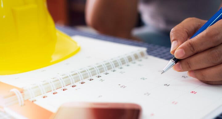 Yellow hard hat and calendar for planning