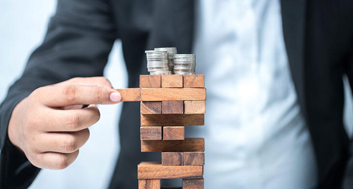 Stack of Jenga blocks with three stacks of coins on top and a man in a suit pulling one of the blocks from near the top of the stack