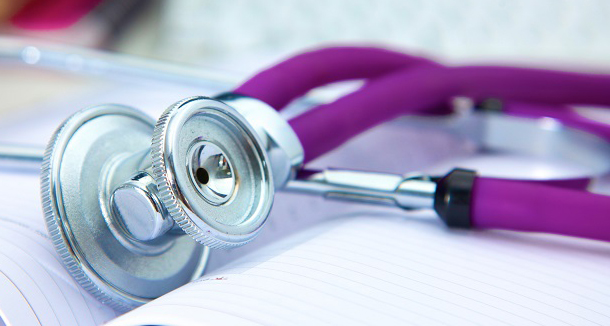 A stethoscope with a purple earpiece on a white lab coat
