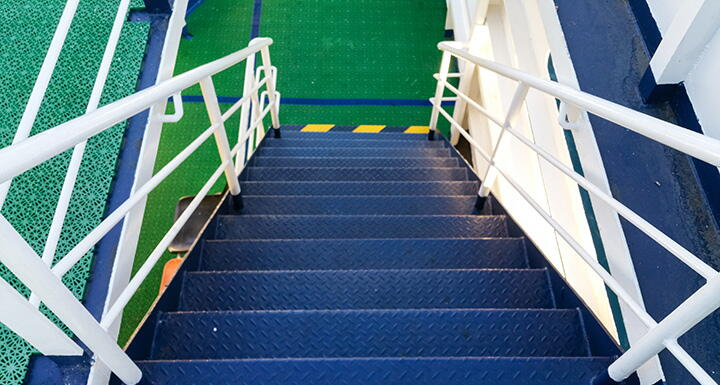Blue staircase with white railing and green landing