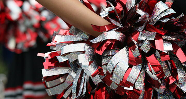 Cheerleader hand holding a red silver and black pom pom behind their back