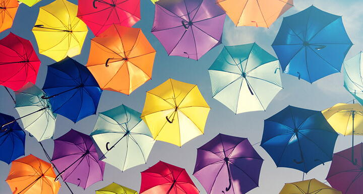 Looking up in the sky at the underside of umbrellas colored yellow red blue purple and orange