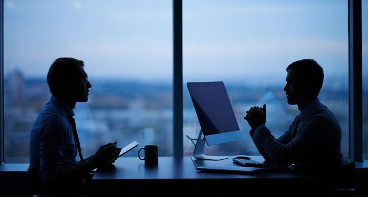 Two shadowy figures talking in front of large office windows