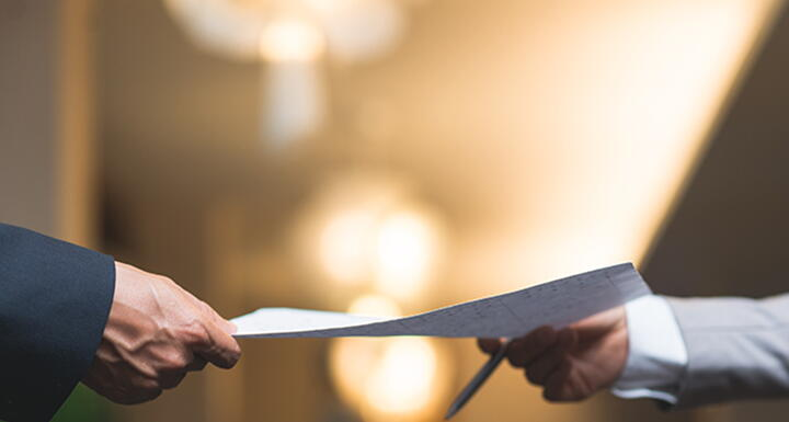 man handing sheet of paper to another person