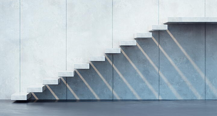 White floating cement staircase against a cement wall