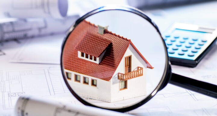 Magnifying glass hovering over house