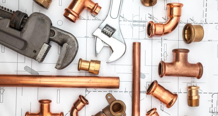Plumbing wrenches and pieces of copper piping on an architectural drawing background