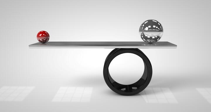 One red ball and one silver ball balancing on a board
