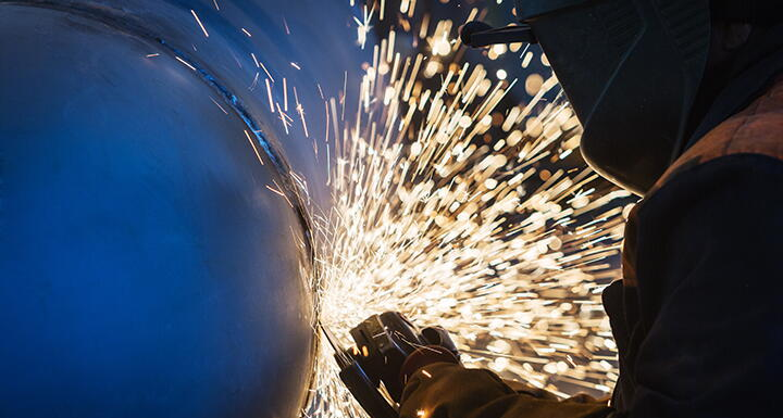 A welder cuts steel and sparks fly