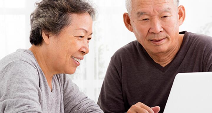 Elderly woman and elderly man looking at laptop screen