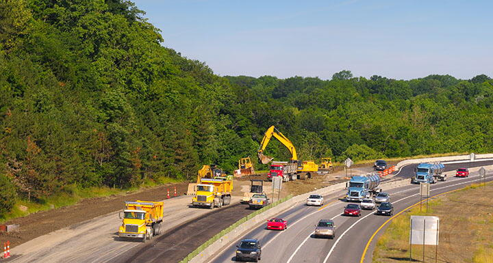 Highway construction with cars, trucks, and equipment