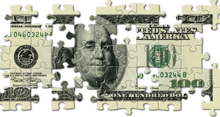 One hundred dollar bill cut into puzzle pieces with several of the pieces missing