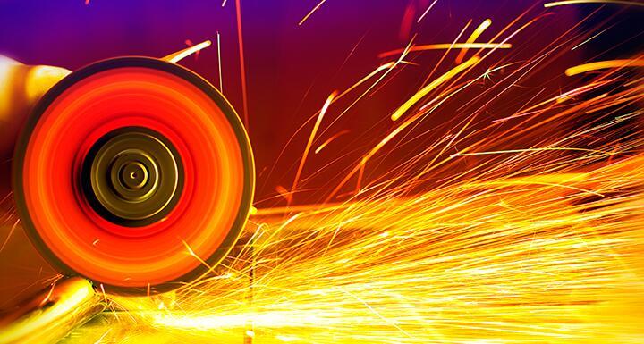A metal circular saw going through sheet metal with sparks flying