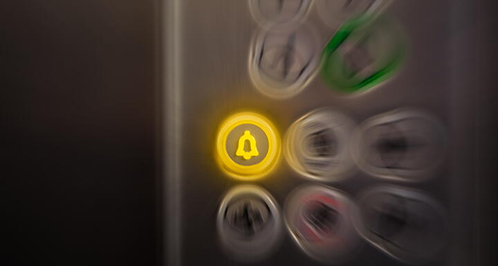An alarm button lit in yellow in an elevator