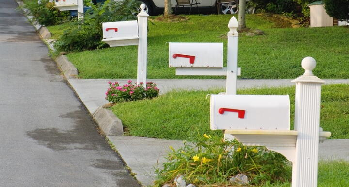 Row of three white mailboxes and neatly trimmed lawns to illustrate restrictive covenants