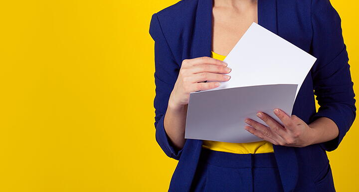 Woman in blue suit shifting through papers