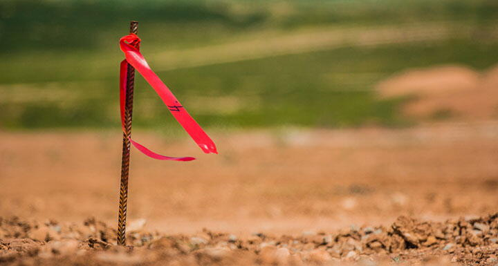 A surveyor's stake with a red flag in a plot of cleared land
