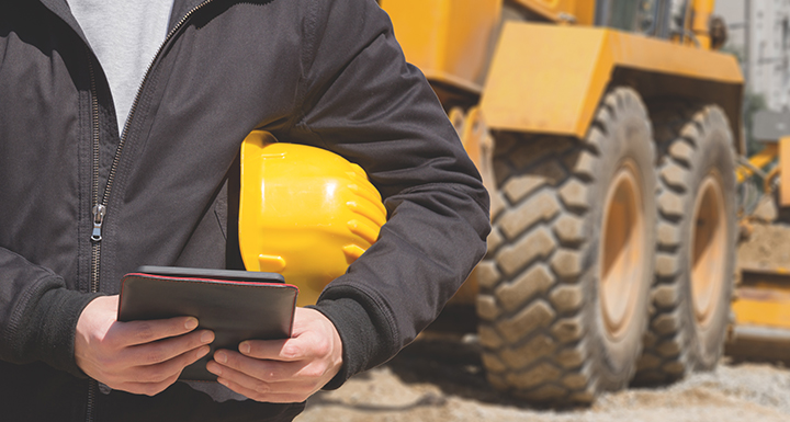 Close up of man with hard hat under arm and tablet in hands on a construction site