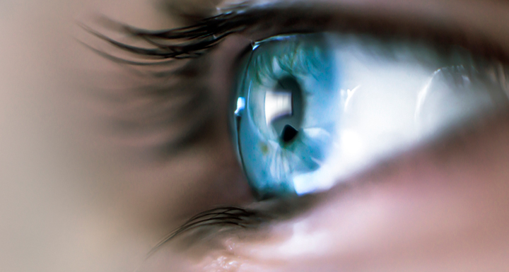 Close up picture of a person's bright blue eye with long eyelashes