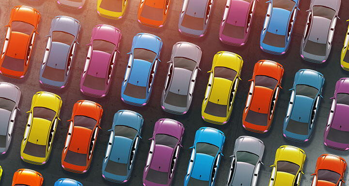 Aerial view of cars of various colors parked together in a parking lot