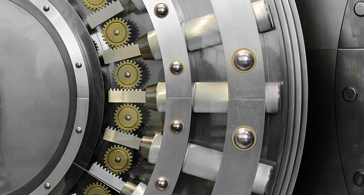 A close-up of a polished steel bank vault locking mechanism