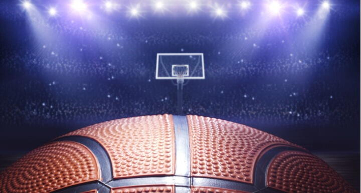 Close up on basketball with basketball hoop in arena