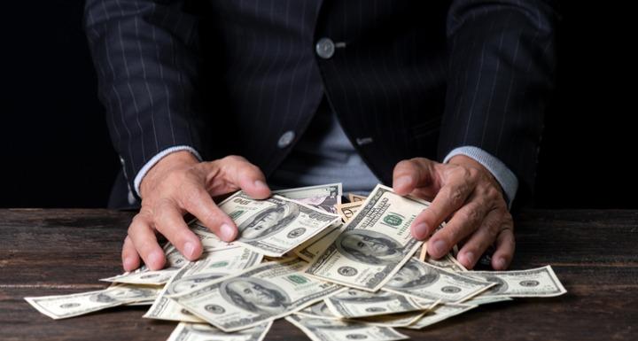 Man in Suit sweeping money into his hands