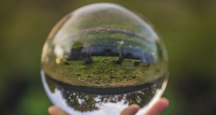 crystal ball with inverted image of green natural landscape