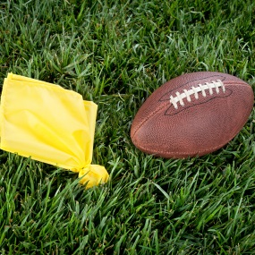 Yellow flag and football on grass